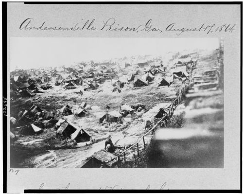 "This photo of Andersonville shows the ""dead line"" prisoners were forbidden to cross--the fence at right. Crossing it meant being shot, an option attractive for those who had had enough of Andersonville."
